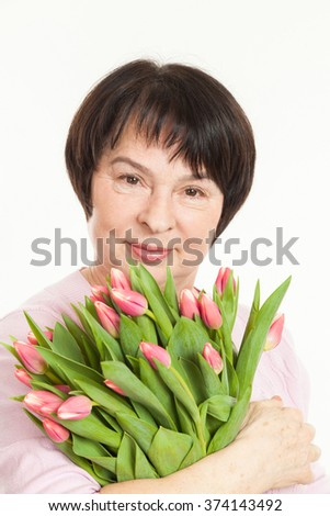 the beautiful mature woman with a bouquet of tulips - stock photo