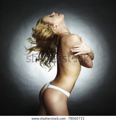 The beautiful naked sports blonde woman on a black background - stock photo