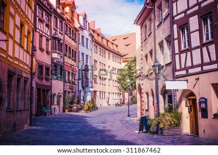 The beautiful place and sunshine, sunny summer day. Typical european styles alleyway in Nuremberg, Bavaria, Germany. The area has many restaurants and cafes. A peaceful, romantic and heavenly place. - stock photo