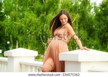 The beautiful pregnant woman in a dress in green foliage - stock photo