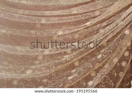 The beautiful transparent tulle decorated with an embroidery and draped in the form of folds. - stock photo