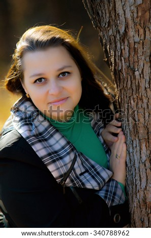 The beautiful woman costs near a tree in autumn park and smiles.