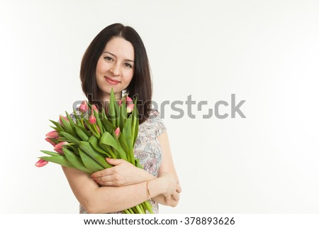 the beautiful woman holds a bouquet of tulips