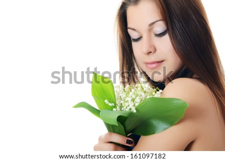 The beautiful woman holds a flower of a lily of the valley