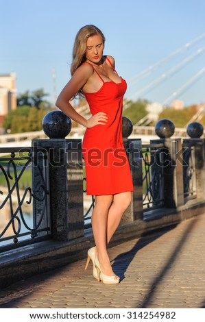 The beautiful woman in elegant red dress in the summer city
