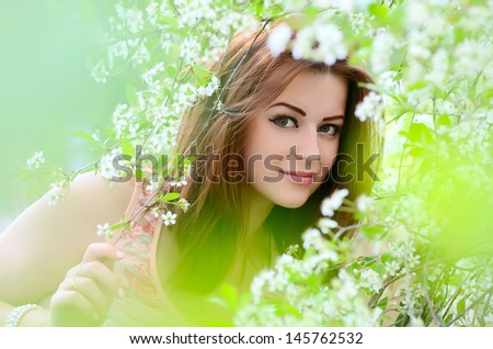 The beautiful woman in flowers of cherry - stock photo