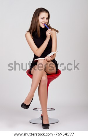 The beautiful woman in glasses with pen and notebook in chair - stock photo