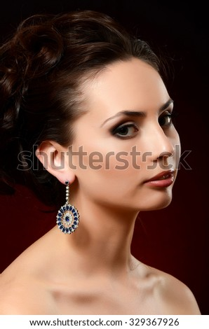 The beautiful woman in jewelry earrings close-up