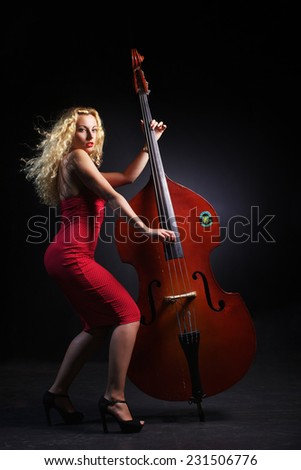 The beautiful woman is play on the contrabass  - stock photo