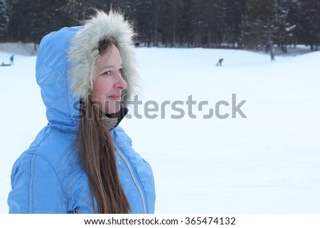 The beautiful woman with long hair in a blue jacket with a hood against snow and the wood in the winter - stock photo