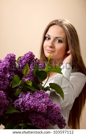 The beautiful woman with spring bouquet of lilac