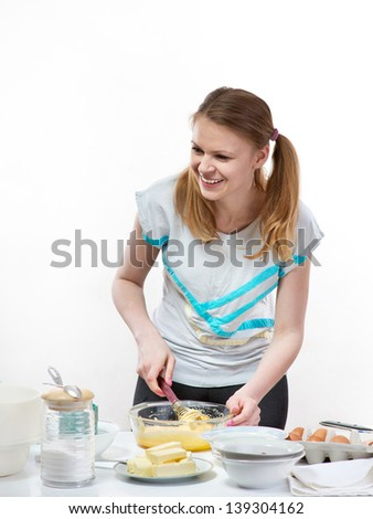 The beautiful young cheerful girl on home cuisine cooks dough for easter pie