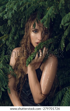 the beautiful young girl with long hair costs in foliage in the rain, with a hand holds a branch with foliage about lips