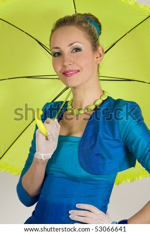 The beautiful young lady costs in a blue dress under a green umbrella in style of a retro - stock photo