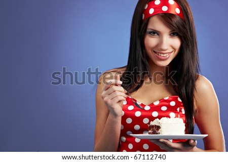 The beautiful young woman eat a slice of a sweet cake - stock photo