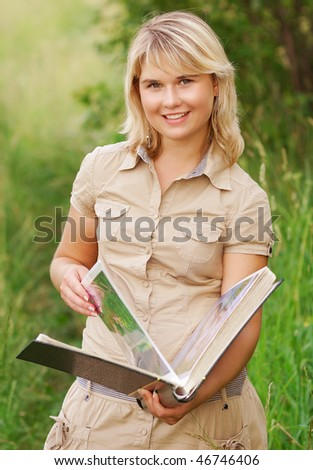 The beautiful young woman holds a picture album in hands and smiles, against a summer landscape.