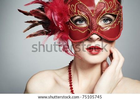 The beautiful young woman in a red mysterious venetian mask - stock photo