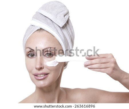 The beautiful young woman in towel with a cosmetic cream - stock photo