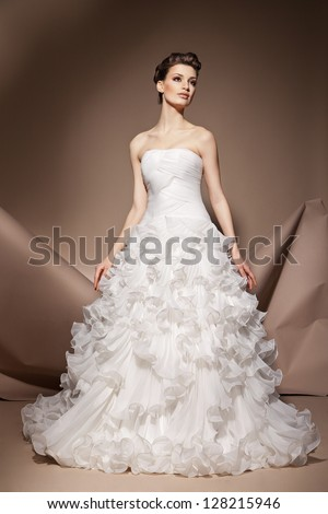 The beautiful young woman posing in a wedding dress - stock photo
