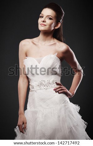 The beautiful young woman posing in a wedding dress on a grey background