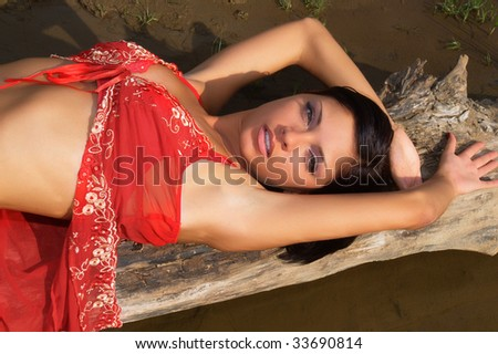 The beautiful young woman relaxing on a tree