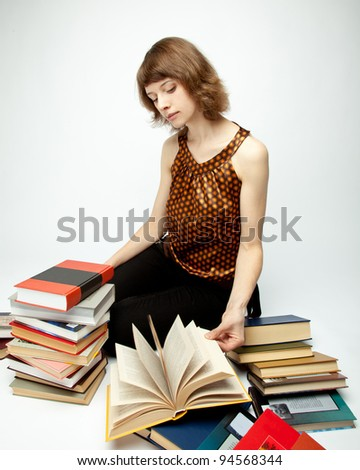The beautiful young woman sitting among books and turning pages; neutral background