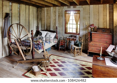 The bed room in a primitive colonial style reproduction home, built with materials reclaimed from structures built in the late 1700's.  The room contains many antiques from the late 18th century. - stock photo
