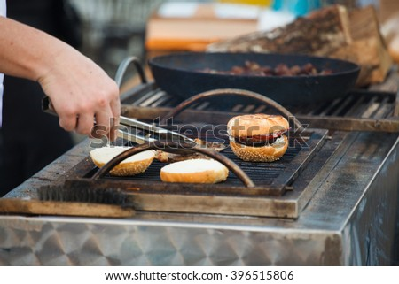 the beef burger with bun on the hot grill. Good snack for outdoors party or picnic