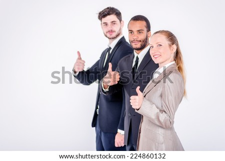 The best employees. Three confident and successful businessman standing in a row while businessman showing a thumbs up on a gray background - stock photo