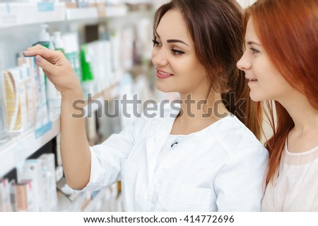 The best for you. Portrait of a pharmacist offering medication product to her female customer. - stock photo