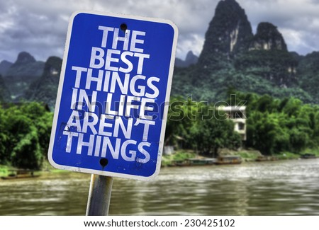 The Best Things In The Life Aren't Things sign with a forest background - stock photo
