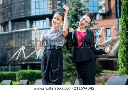 The best women in the company. Two young businesswoman talking on the street and enjoyed their success while standing in front of an office building in the park - stock photo