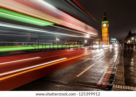 The Big Ben at night, london, UK with a typical bus passing by - stock photo