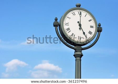 The big figured street clock against the blue sky - stock photo