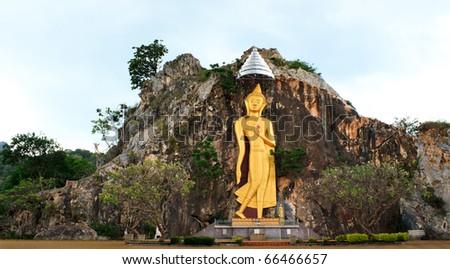 The Big Golden Buddha on stone mountain in Ratchaburi, Thailand - stock photo