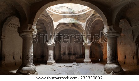 The big hall of the ancient Christian temple Geghard with a dome and columns. - stock photo
