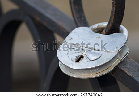 the big old iron padlock of silvery color is locked on the forged fencing - stock photo