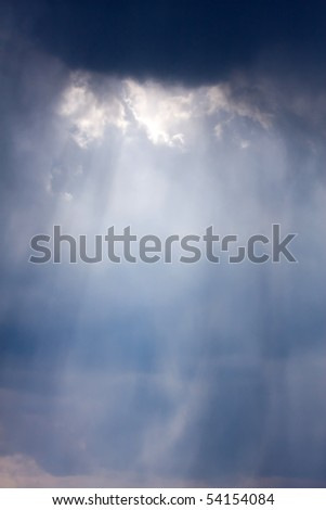 The big powerful storm clouds with sunlight - stock photo