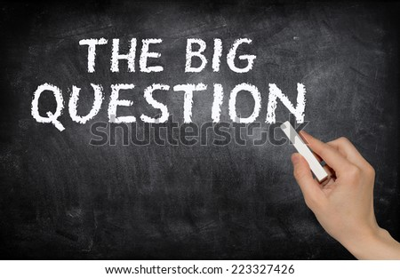 The big question, written with white chalk on a blackboard - stock photo
