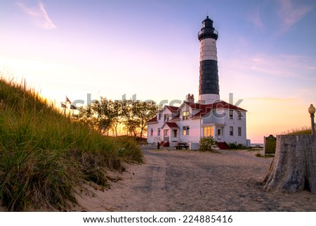 The Big Sable Lighthouse illuminated by the golden rays of the setting sun. Ludington State Park. Ludington, Michigan. The lighthouse is only accessible by foot after a mile and a half hike. - stock photo