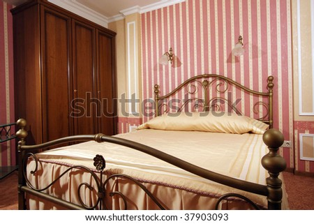 The big wide bed in a convenient modern bedroom - stock photo