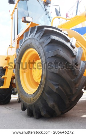 The big yellow wheel of heavy tractor - stock photo