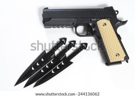 The black gun and throwing knives on a white background. Still life with the gun and knives on a white background. - stock photo