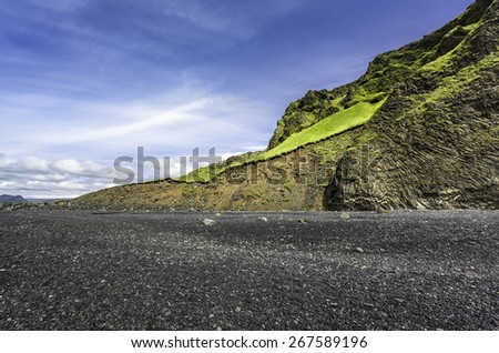 The black sand beach with typical Icelandic mountain landscapes