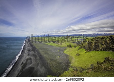 The black sand beach with typical Icelandic mountain landscapes aerial view