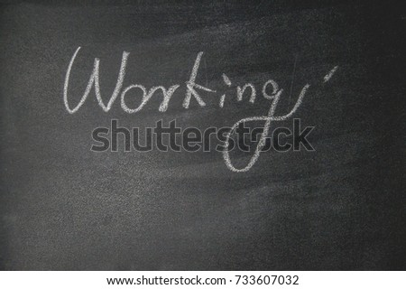 "The blackboard writing with chalk and the concept of business and finance, Blackboard with chalk to write the text ""WORKING"""