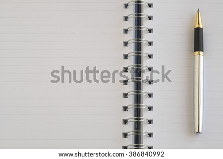 The blank notebook and a silver pen. - stock photo