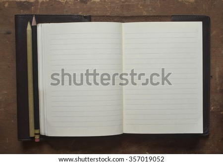 The blank page of a leather bound journal lies open on a vintage desk. - stock photo