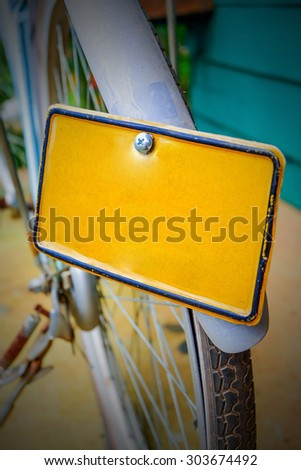 The blank yellow license plate of the vintage bicycle - stock photo
