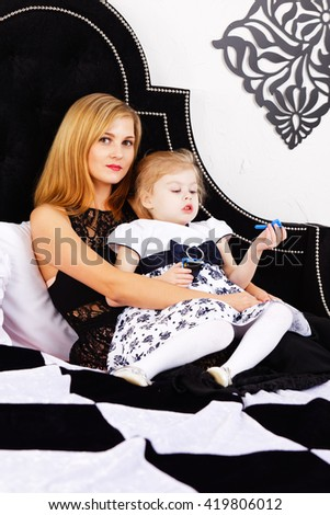 The blonde in a black evening dress with a child lying on the bed. Mom and daughter. - stock photo